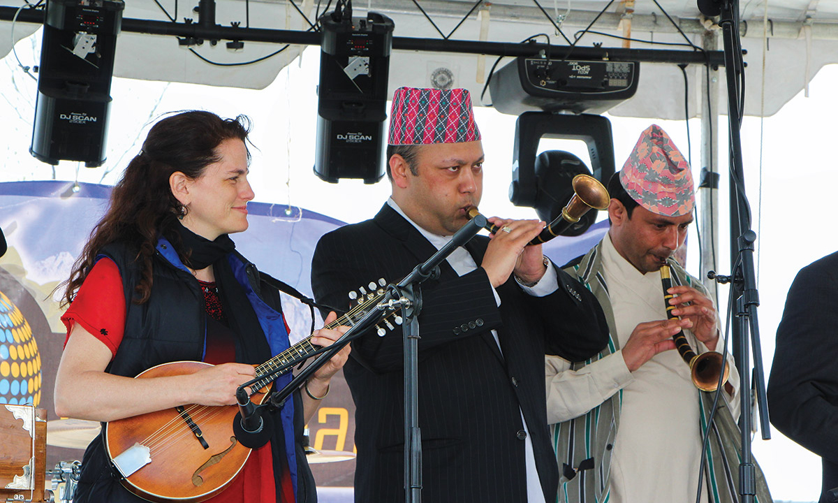 Tara Linhardt plays mandolin on stage alongside two Tibetan musicians.