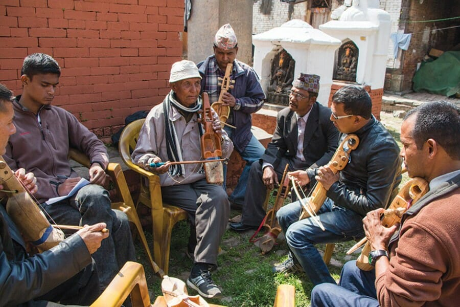 Several Tibetan musicians play instruments together in a circle outside.