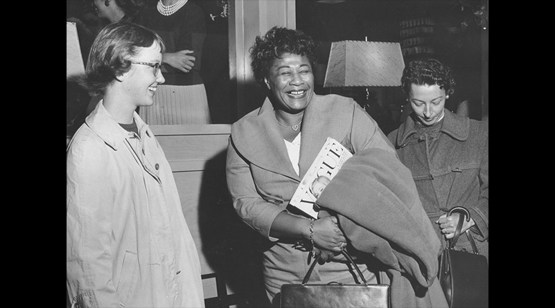 Black and white photo of Ella Fitzgerald with two students.