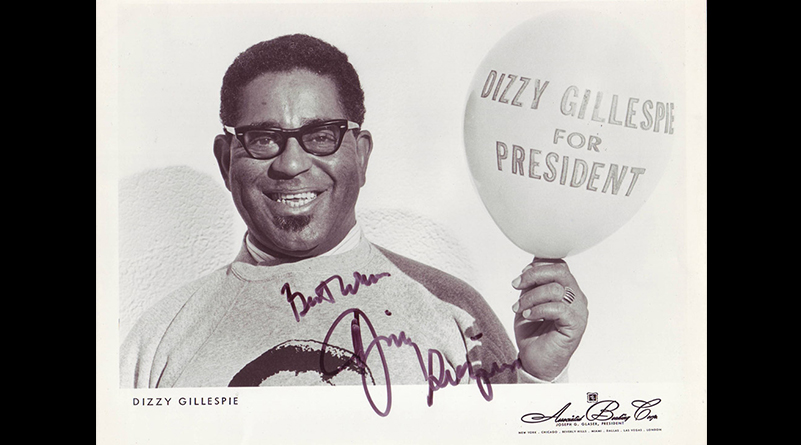 Black and white autographed photo of Dizzy Gillespe holding balloon with words