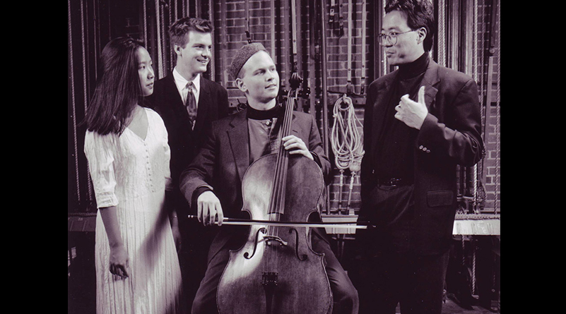 Black and white photo of Yo Yo Ma speaking with group of three people, one of whom is holding a cello