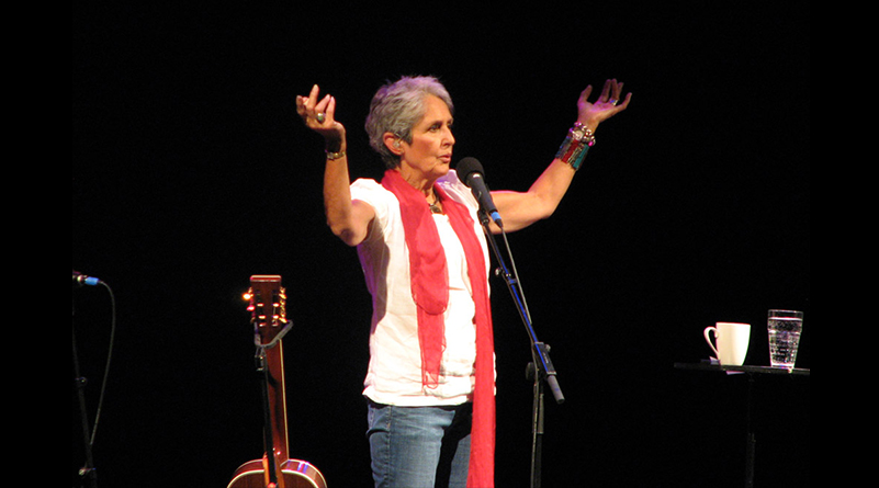 Joan Baez stands on stage
