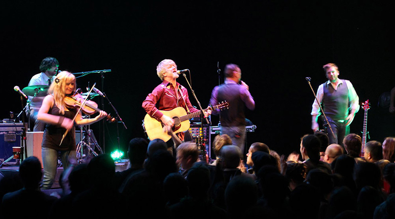 Five-member band, including a guitarist, singer, and fiddle player perform onstage