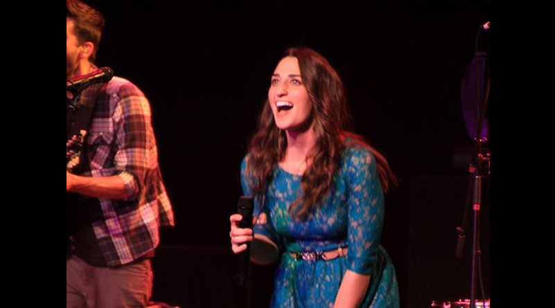 Sarah Bareilles smiling and holding microphone onstage