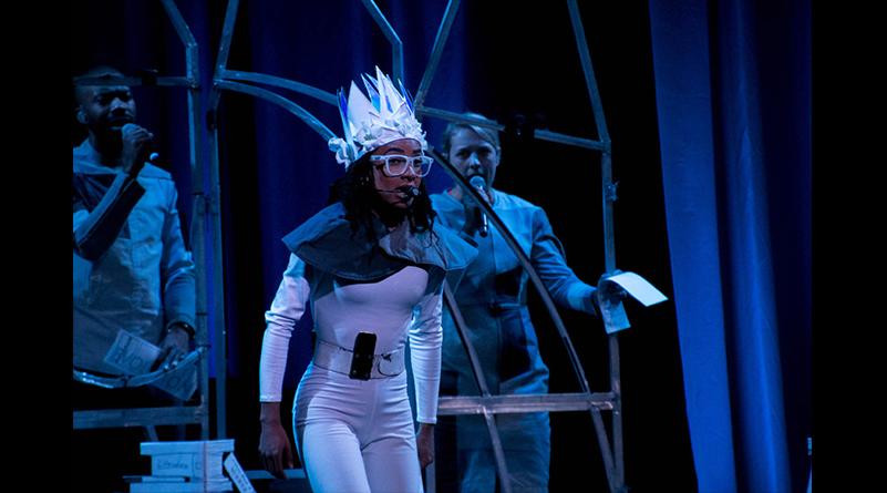 Esperanza Spalding wearing white costume performs under dramatic stage lighting