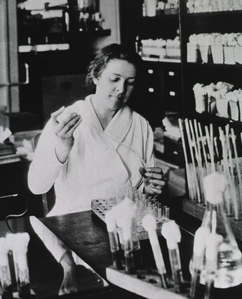 Black and white photo of Alice Evans in lab filling test tubes.