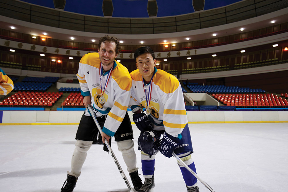 Alex Frecon and teammate wearing hockey gear pose on ice rink with hockey sticks