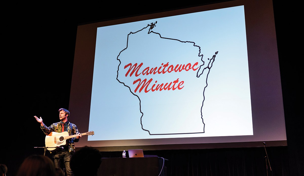"""Charlie Berens stands on stage holding a guitar in front of a projection that reads """"Manitowoc Minute"""""""