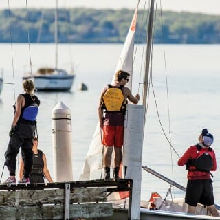 Members of the Hoofers Sailing Club bring their boats to a pier at the Memorial Union Terrace.