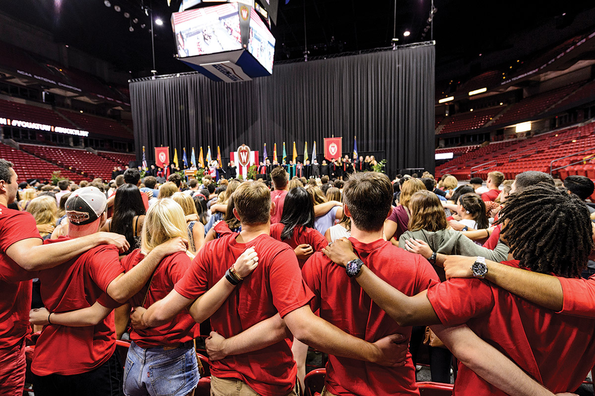 First-year students link arms and sing 'Varsity' at the end of the Chancellor's Convocation for New Students, a Wisconsin Welcome event