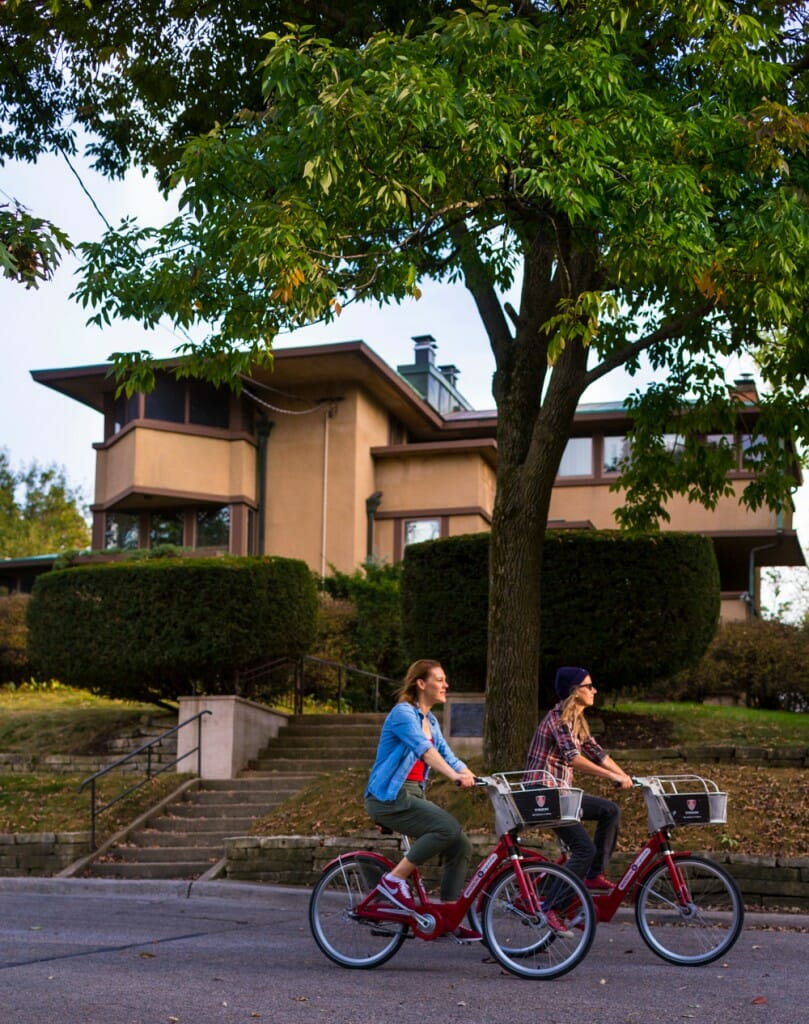 Two bicyclists ride past Frank Lloyd Wright house