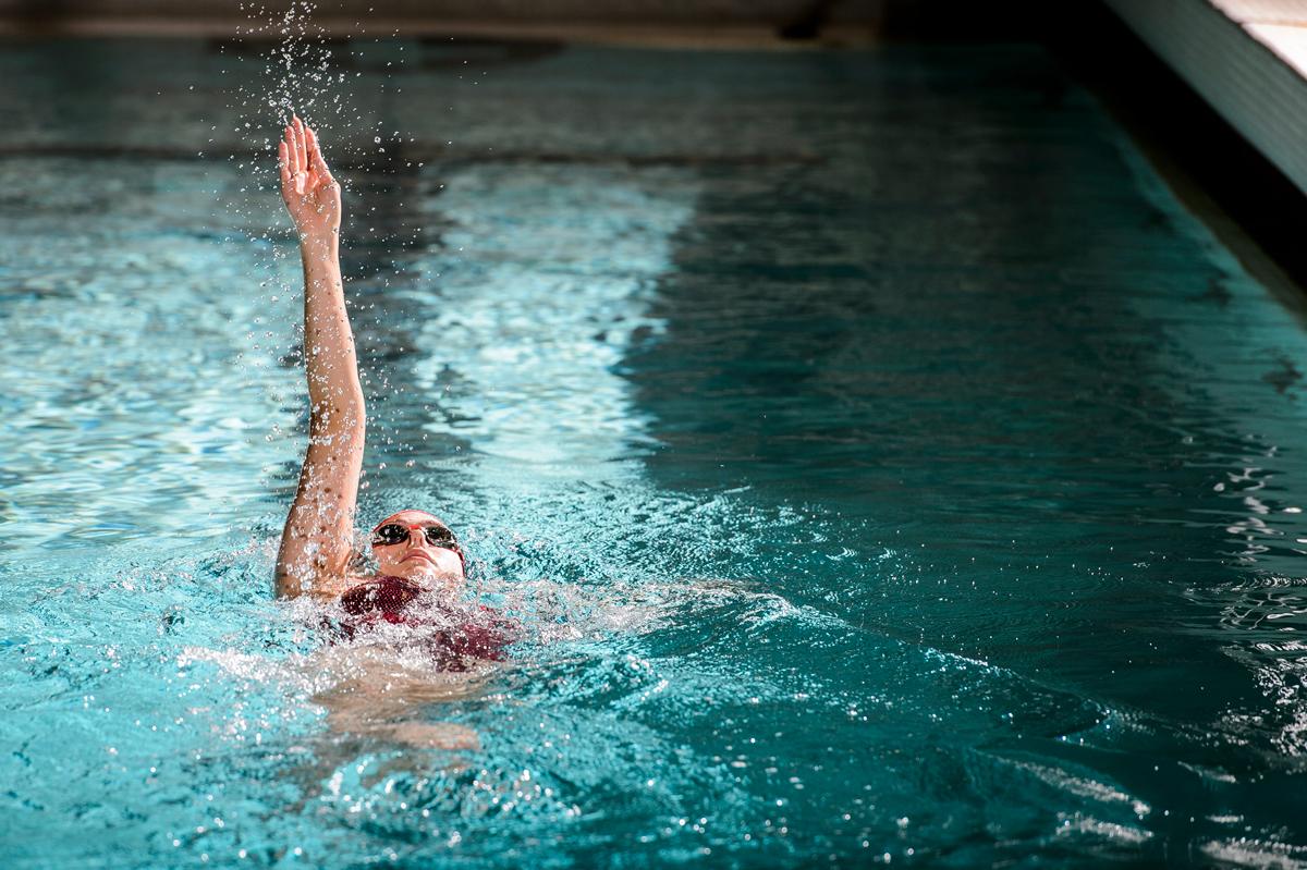 Beata Nelson in pool mid-backstroke