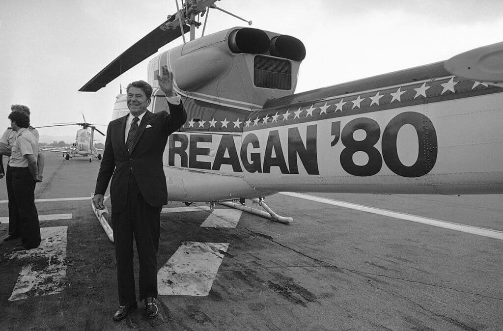 "Ronald Reagan waves to supporters in front of plane with ""Reagan '80"" painted on side"