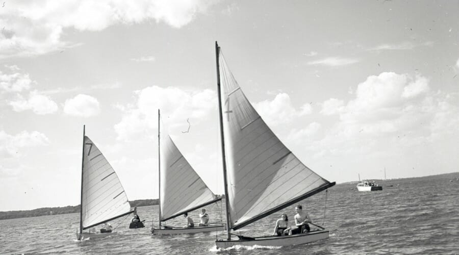 Three pairs of students sail parallel to one another across Lake Mendota in this photo taken in the mid-20th century.
