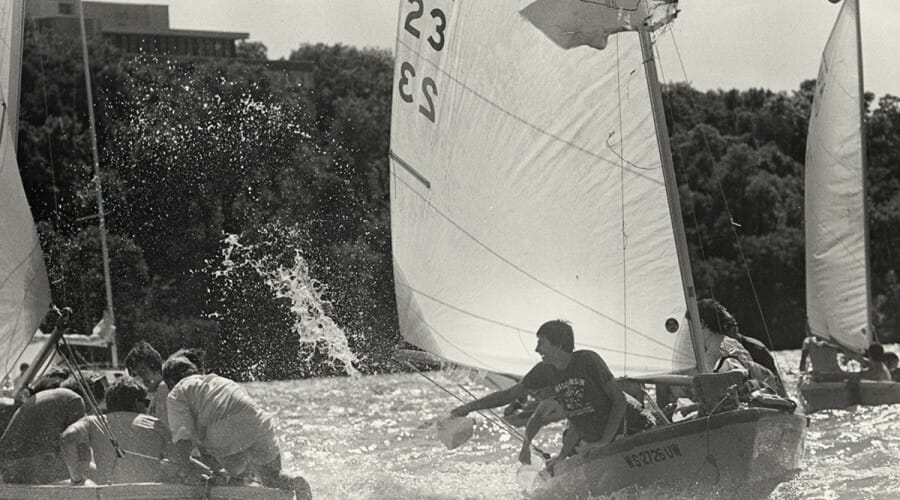 Members of the Hoofer Sailing Club splash each other from two sailboats.
