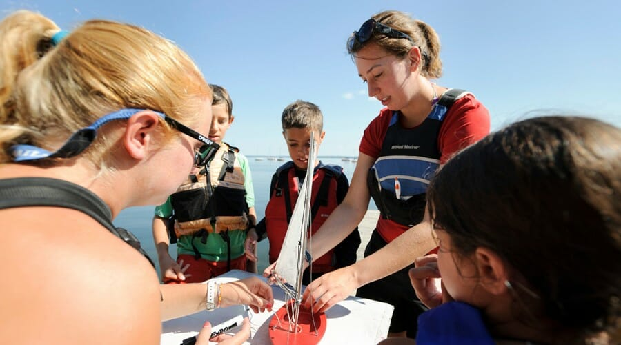 UW students and Hoofers instructors Katlyn Putney '14 and Ella Stutz '13 demonstrate sailing maneuvers in 2012 to children who signed up for a youth sailing program.