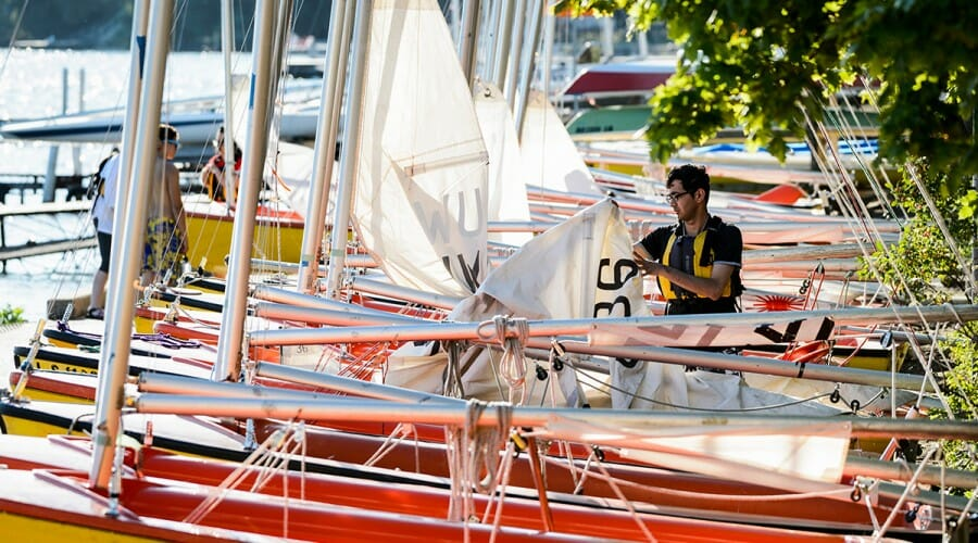 At sunrise, a member of the Hoofer Sailing Club rigs up a sail on a tech boat in July 2016.