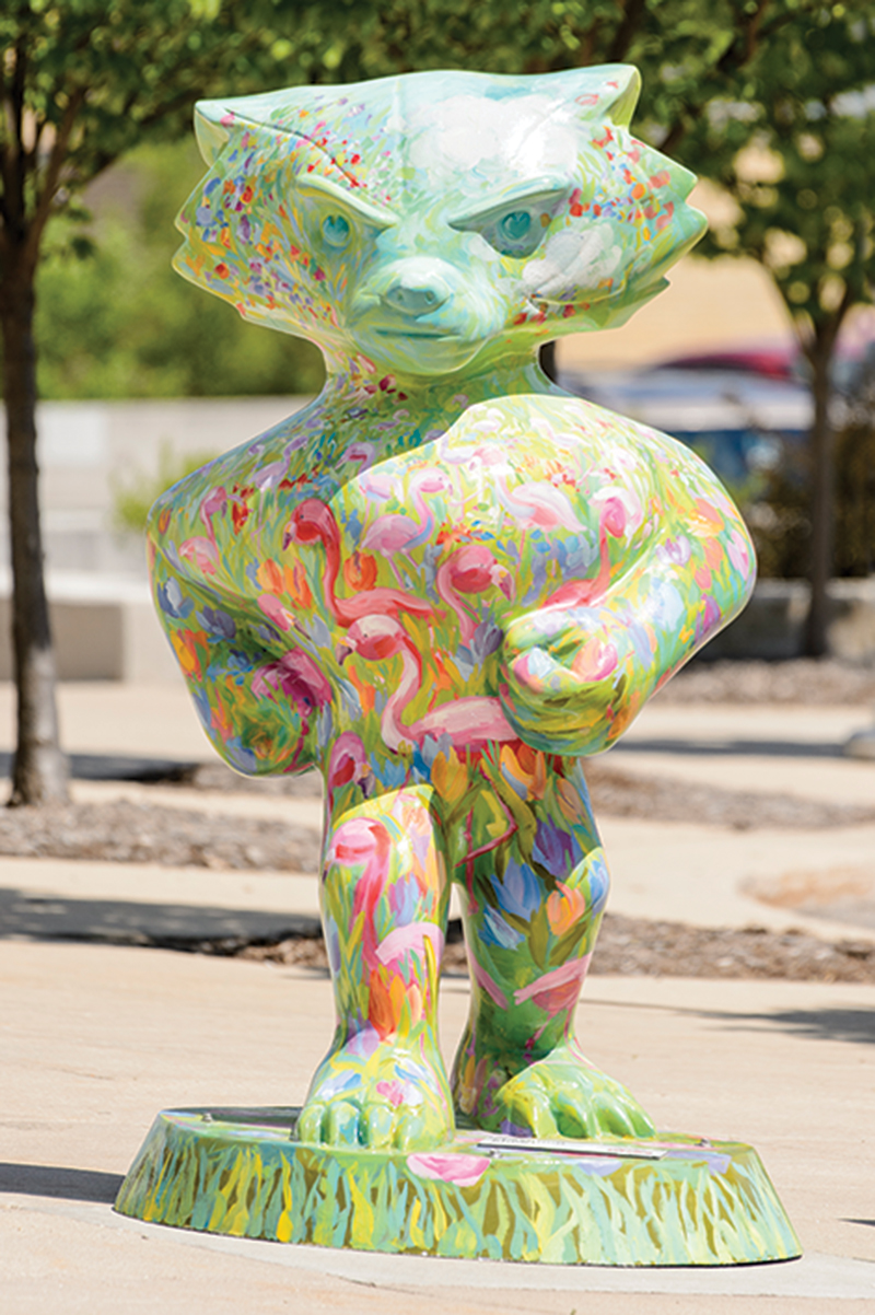 Bucky statue painted green with flowers and pink flamingos