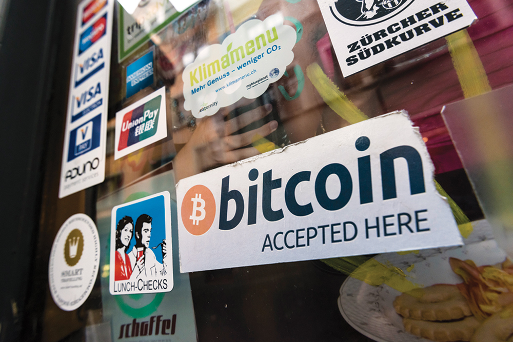 "A store window displays a sign that reads ""Bitcoin accepted here"""