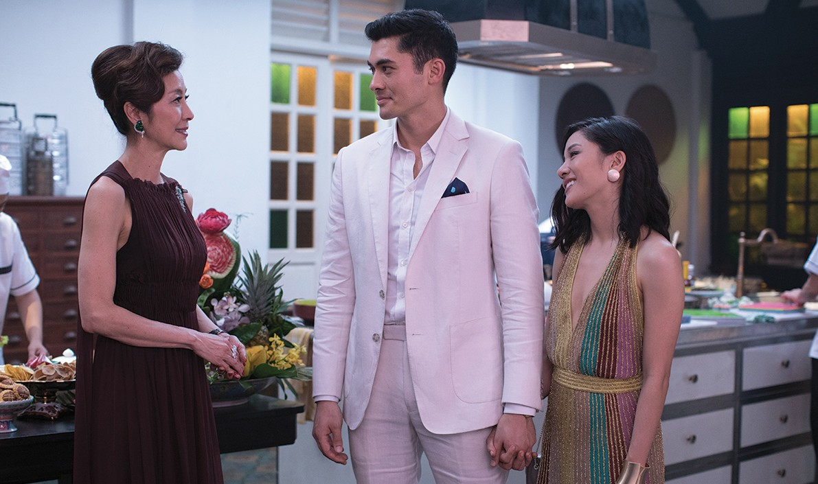 "A scene from the movie ""Crazy Rich Asians"" where two women and a man wearing formal attire converse with one another"