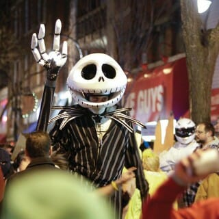 A person wearing a skeleton costume stands among other costumed party-goers on State Street in Madison, Wisconsin