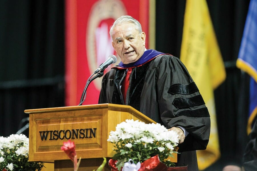 Tommy Thompson gives a speech at the podium at a UW Commencement ceremony