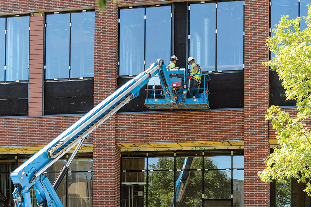 Construction workers standing in a lift inspect second story windows on a campus building
