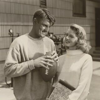 Elroy Hirsch holding a footbal and a female co-star in scene from movie,