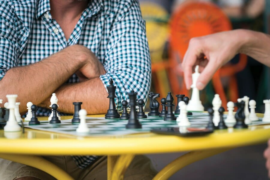 Close-up photo of two people's hands and a chessboard on the Memorial Union Terrace