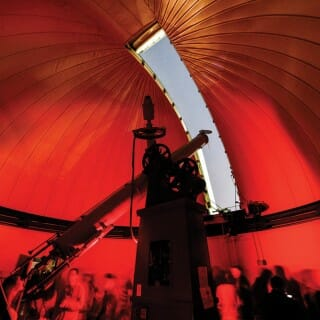 Tourists crowd in the interior of the Washburn Observatory dome that shows a sliver of sky through the open aperture