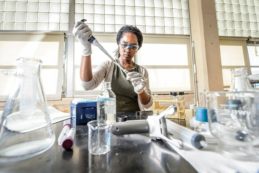 Coty Weathersby working in a lab, filling a test tube