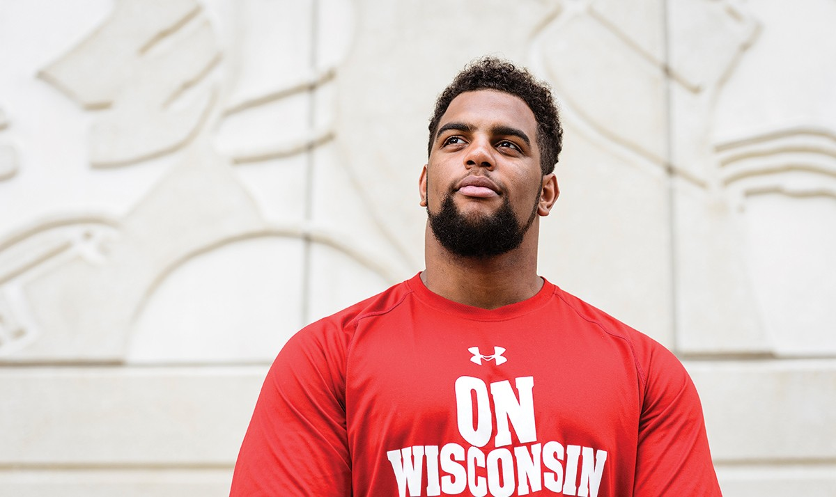 "Portrait of Bryson Williams wearing a red shirt printed with words ""On Wisconsin"""