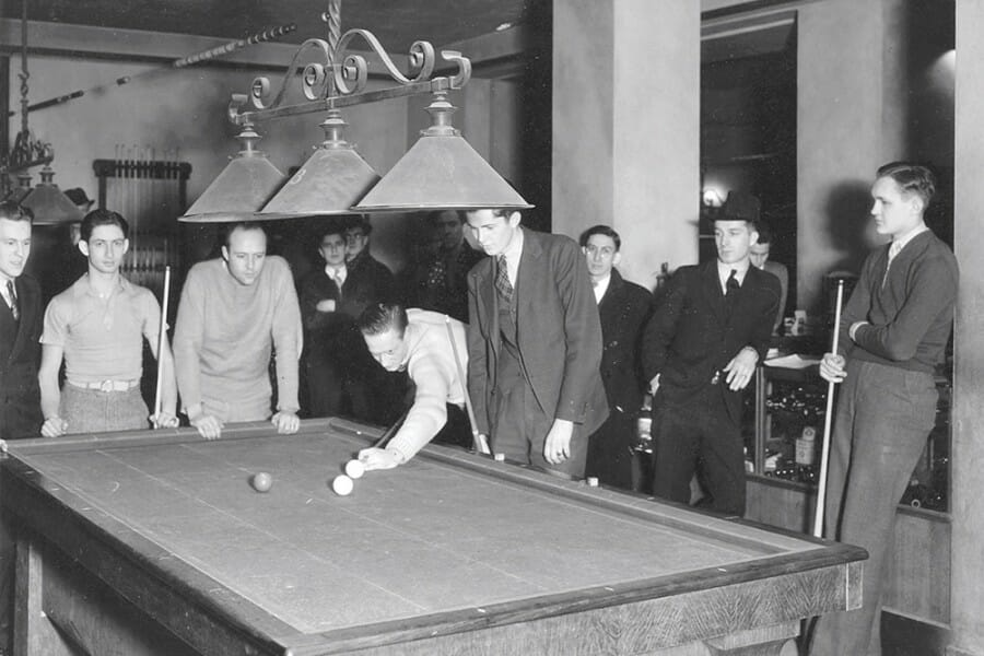 Black and white photo from the 1930s of students playing pool