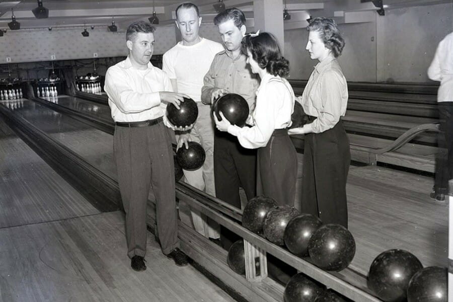Historical black and white photo of a group of students in a bowling alley holding bowling balls
