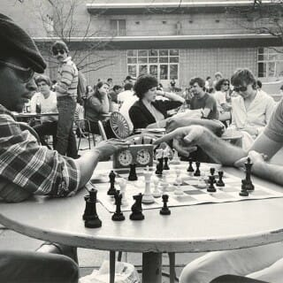 Black and white photo from the 1980s of two students playing a game of chess on the Memorial Union Terrace