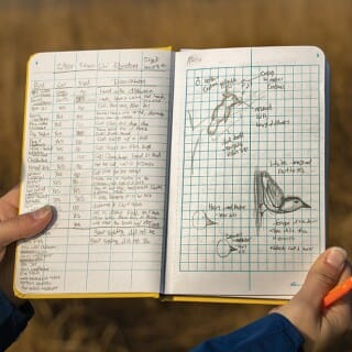 Pair of hands holding notebook filled with birding notes and illustrations