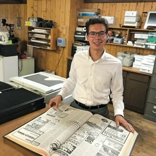 Nash Weiss poses with book of old newspapers