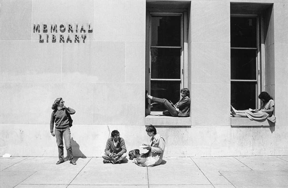 Black and white photo of students sitting outside of Memorial Library on the UW–Madison campus