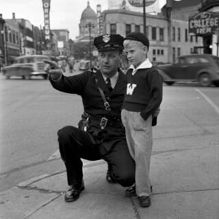 In 1949, Officer Hector Naze poses with a seven-year-old Milverstedt on a State Street corner in Madison, WI