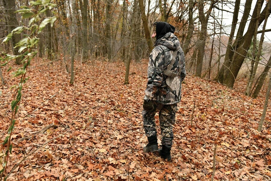 Don Waller walks in woods wearing camouflage