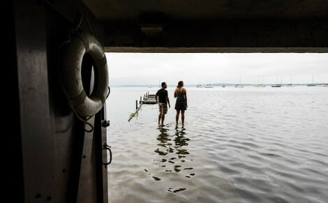 Students appear to walk on water at the flooded limnology pier on Lake Mendota.