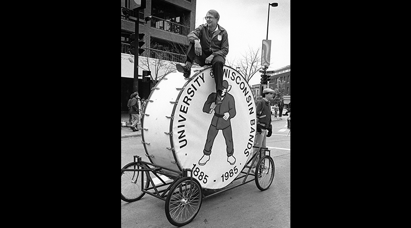 Mike Leckrone sits atop a large drum on wheels at the UW Homecoming Parade on October 1987