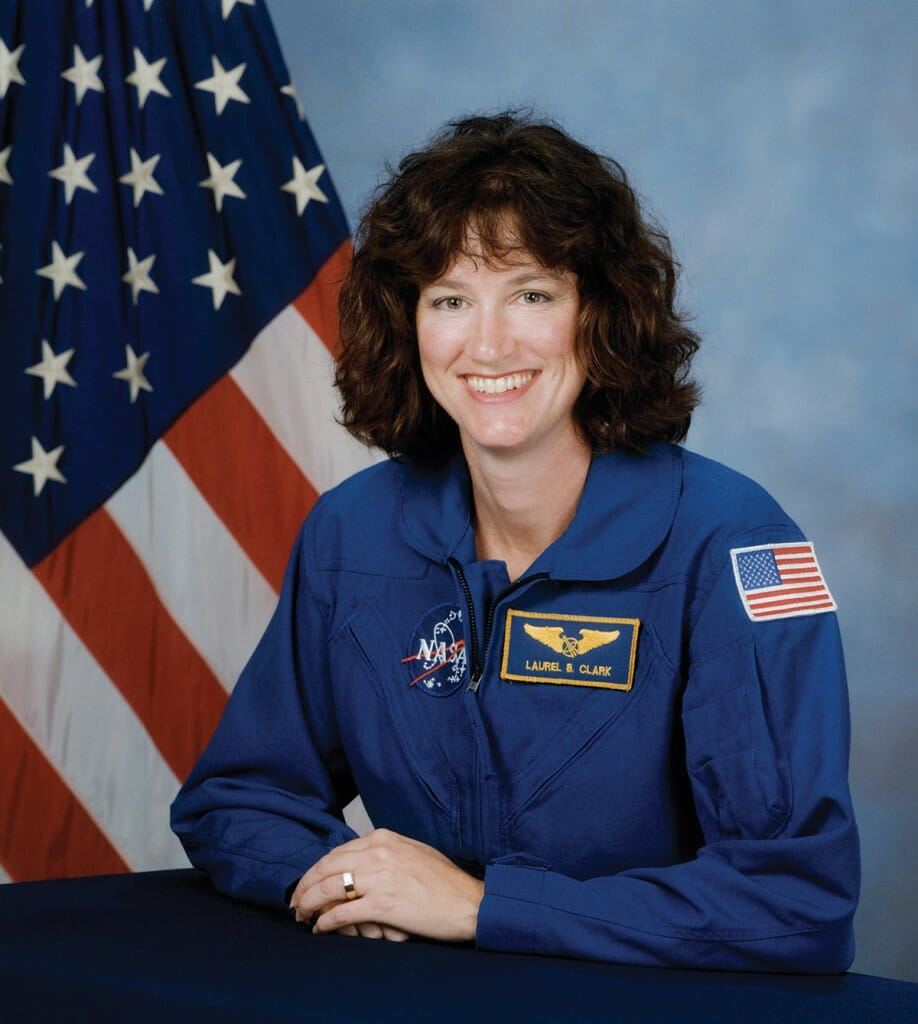 Laurel Clark wearing NASA uniform poses in front of American flag