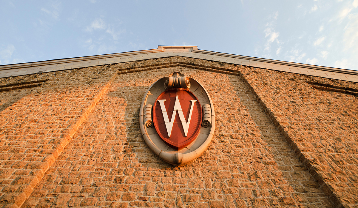 """W"" crest displayed on the side of the UW-Madison Field House"