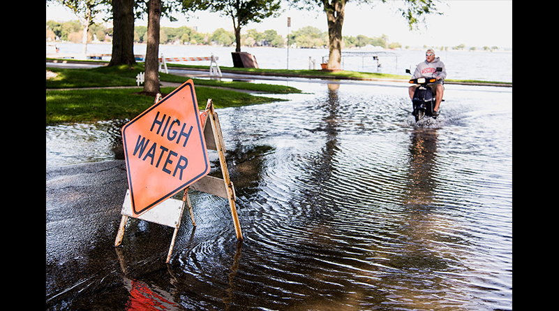 A scooter driver braves high-standing water flooding West Shore Drive along Monona Bay on September 6. Flooding and lane closures persisted for weeks after the initial rainfall, with damage estimates exceeding $150 million throughout the county.