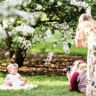 A woman photographs a baby sitting under a flowering tree as the mother looks on at the UW Arboretum
