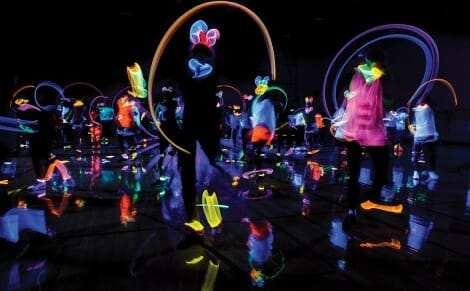 Members of a fitness class move around in a dark gym, wearing glow-in-the-dark accessories