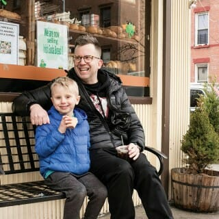 Jason Gay and his son, Jesse, seated on a bench in front of a bakery in Brooklyn, New York