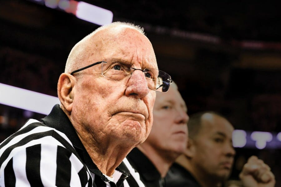 Otto Puls wearing his black and white striped referee uniform watches a basketball game