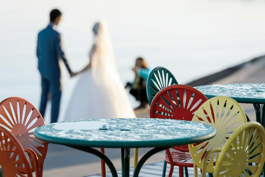 A bride and groom pose for photographs at the Memorial Union Terrace